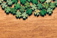 Wooden green shamrocks laying on the wooden floor. St. Patrick`s Day. Symbol of luck Stock Images