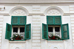 Wooden green window shutters and red flowers on a house Stock Photos