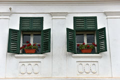 Wooden green window shutters and red flowers on a whitewashed ho Royalty Free Stock Photo