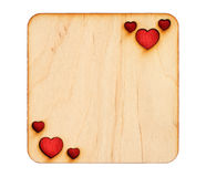 Wooden greeting card with scorched hearts with red paper inside. Isolated on white background Stock Image