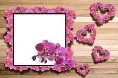 Wooden greeting frame with orchids. Square frame for congratulation from orchid flowers with orchids scattered over the surface photo orchid hearts on a wooden Royalty Free Stock Image