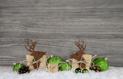 Wooden grey christmas background with reindeer, balls and gifts Stock Photos