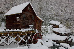 Wooden grist mill in Winter. Scenic view of snow covered wooden grist mill in Winter, forest in background Royalty Free Stock Image