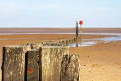 Wooden groyne on Cleethorpes beach with wind turbines in the distance stock photos