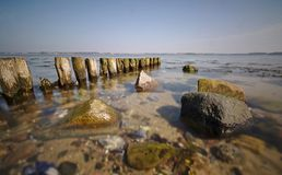 Wooden groyne leading out to sea with shallow water and rocks in the foreground long exposure stock photos