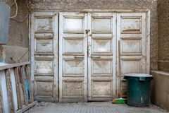 Wooden grunge weathered white painted abandoned door, green trash can and ladder Stock Images