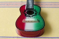 Wooden guitar toy. On typical yellow tablecloth from Oaxaca, Mexico. Traditional mexican toys