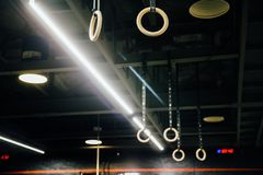 Wooden Gymnastic rings in the interior of the gym loft. Nobody. Spacious gym with rings and ropes for trainings. Place for the text Stock Images