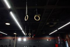 Wooden Gymnastic rings in the interior of the gym loft. Nobody. Huge air gym is a black ceiling royalty free stock photos