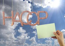 Wooden HACCP text Stands for Hazard Analysis and Critical Control Point hanging on rope and businessman hold a green paper. Wooden HACCP text Stands for Hazard royalty free stock image