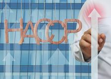 Wooden HACCP text Stands for Hazard Analysis and Critical Control Point hanging on rope and businessman point to the top of arrow. Wooden HACCP text Stands for royalty free stock image