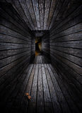 Wooden hallway. A creepy long crooked hallway made of wood and extending down into the earth Royalty Free Stock Photography