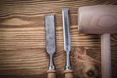 Wooden hammer firmer chisels on vintage wood board construction Stock Image