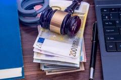 Wooden hammer, handcuffs and euro bills, laptop Stock Image