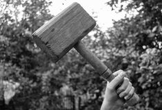Wooden hammer in his hand raised up. Black and white photograph of a wooden hammer in his hand, like a hammer Torr Stock Photos