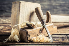 Wooden hammer and planer in a carpentry workbench. On old wooden table Stock Photography