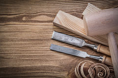 Wooden hammer stud firmer chisels planning chips on vintage wood Royalty Free Stock Images