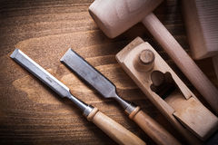Wooden hammers planner flat chisels on wood background construct Royalty Free Stock Photos