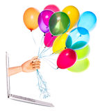 Wooden hand with balloons and laptop Royalty Free Stock Photo