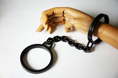 Wooden hand in handcuffs Stock Images