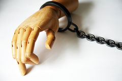 Wooden hand in handcuffs Stock Image