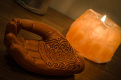Wooden Hand with Henna Engravings and a Himalayan Rock Salt Candle Stock Photo