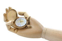 Wooden hand holding antique, gold pocket watch. Wooden hand holding an antique, gold pocket watch. The cover is open. The white face features yellow and blue Stock Photography