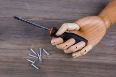Wooden hand holding a phillips screwdriver. Wooden and holding a phillips screwdriver on a wooden  background Royalty Free Stock Photography
