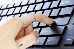 A wooden hand is typing Stock Image