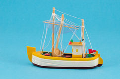 Wooden handmade boat ship model on blue background Stock Photo