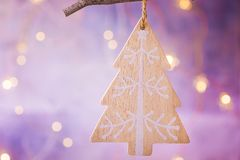 Wooden handmade Christmas tree ornament hanging on branch. Shining garland golden lights. Purple background. Magical atmosphere. Royalty Free Stock Image