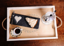 Wooden handmade tray on a brown table. Dessert cake, heart of icing sugar, coffee and geyser moka. Royalty Free Stock Photos