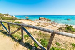 Wooden handrail by the sea in Costa Rei Royalty Free Stock Images
