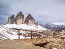 Wooden handrail and sign on trekking path at Dolomites mountains. Wooden handrail and sign on trekking path at the Dolomites mountains at the Italy. Tre Cime di royalty free stock photo