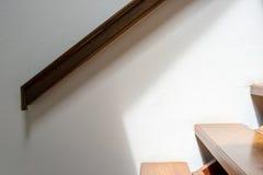 Wooden handrail and stairway. Dark brown wooden handrail and light brown stairway royalty free stock photos
