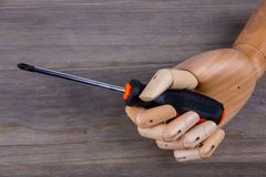 Wooden hands and screwdriver. On White background stock images