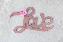 Wooden handwritten sign love on concrete Stock Photo