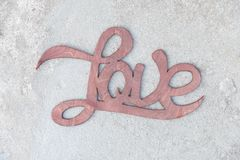 Wooden handwritten sign love on concrete background Royalty Free Stock Photos