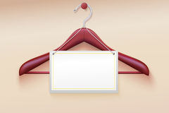 Wooden hanger with tag  on cream background. Royalty Free Stock Photos