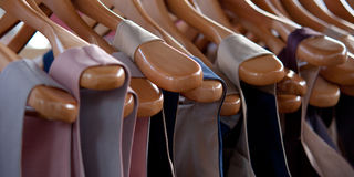 Wooden hangers with clothes. Many wooden hangers with fashionable beautiful dresses Stock Image
