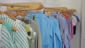 Wooden hangers with fashionable colorful clothes on rack stock video
