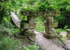 Wooden hanging bridge in the garden. Entrance to the bridge is d. Wooden hanging bridge. Entrance to the bridge is decorated with stone arch support Stock Photo