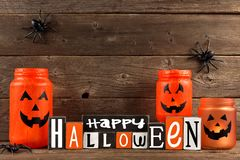 Wooden Happy Halloween sign with Jack o Lantern jars Royalty Free Stock Photos
