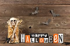 Wooden Happy Halloween sign with jar of bones. Against a rustic old wood background Stock Photos