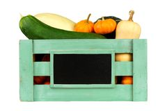 Wooden harvest crate with autumn vegetables over white. Green wooden harvest crate with autumn vegetables and blank chalkboard label isolated on white Stock Photography