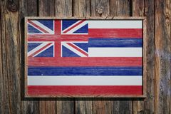 Wooden Hawaii flag. 3d rendering of a Hawaii State USA flag on a wooden frame and a wood wall Royalty Free Stock Photo
