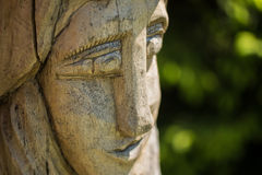 Wooden head in a garden. With blurred background Stock Image