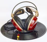 Wooden headphones arranged over some old 33 rpm. Records Stock Photo