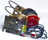 Wooden headphones stuck in the slot sound card printed circuit board. Stock Image