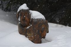 Wooden Heads - Sculpture in Wood Covered in Snow, Izera Mountains, Czech Republic, Europe. Wooden Heads Covered in Snow - Sculpture Nearby Turistic Path in Wood Royalty Free Stock Photos